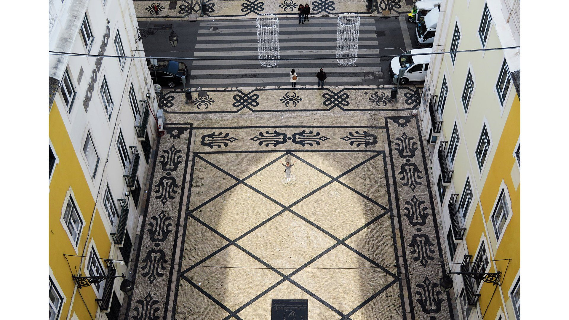 A shot taken from the top of a high building shows a pretty old courtyard with patterned tiled floors and a staircase. On the left and right are yellow and white building fronts.